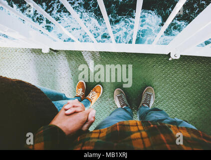 Couple in love Man and Woman feet holding hands standing together above sea Traveling by ship family lifestyle concept romantic vacations cruise journ - Stock Photo