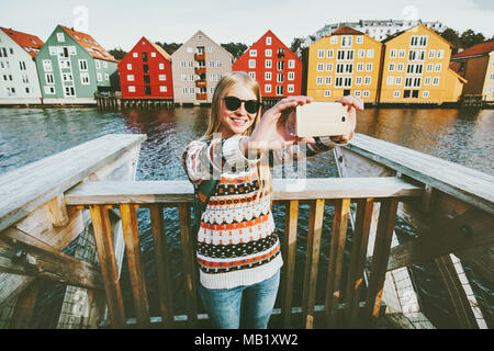 Happy smiling woman taking selfie  traveling in Trondheim city Norway vacations weekend Lifestyle fashion outdoor scandinavian houses landmarks archit - Stock Photo