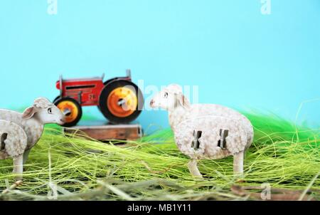 two sheep and a tractor. farm animals with green and blue background. small carton toys for childrens and copy space. - Stock Photo