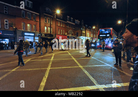 Marchers from the grassroots community organisation, GANG (Guiding A New Generation) joining hands and forming a circle to stop traffic in Hackney Central, London, United Kingdom.  The demonstration follows the death on Wednesday (04.04.2018) of 18-year-old Israel Ogunsola who was stabbed to death and died in Link Street, Hackney. Police found him wounded after they were alerted by a motorist just before 8.00pm.   He was given first aid by police officers, but died at the scene at 8.24pm. He was initially thought to be aged in his 20s.  GANG is a youth outreach movement which focusses on the b - Stock Photo