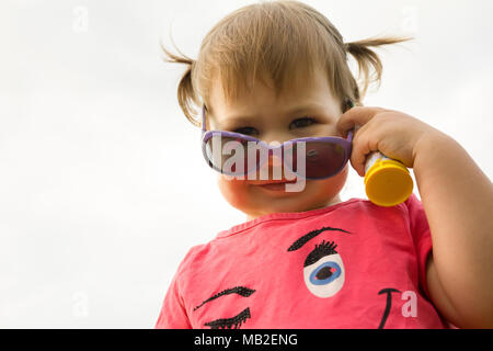 Little hild girl playing in park in front of green grass
