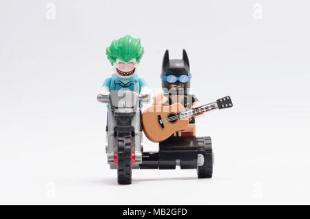 lego joker with batman holding a guitar riding motorcycle. isolated on white background. - Stock Photo