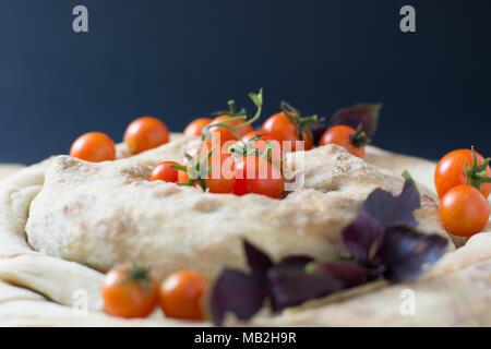 spiral filo pie burek with cherry tomatoes on wooden table - Stock Photo