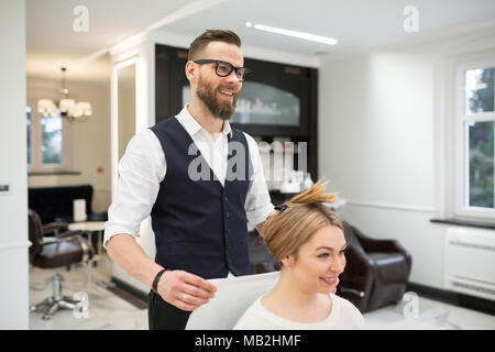 Portrait of happy hairdresser putting towel on client arms - Stock Photo