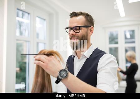 Portrait of happy hairdresser combing customer hair - Stock Photo