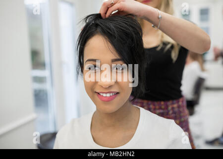 Portrait of young woman having hair styling in salon - Stock Photo