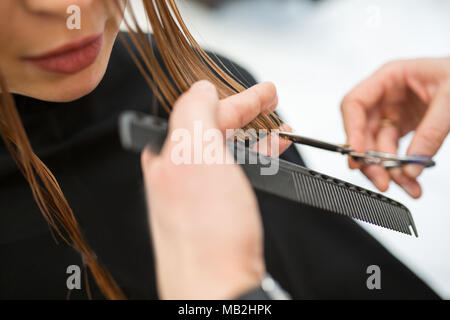 Close up portrait of hairdresser hands cutting young girl hair - Stock Photo