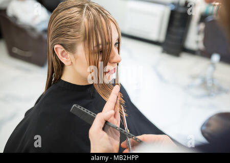 Portrait from above of young woman having her hair cut at hairdresser - Stock Photo
