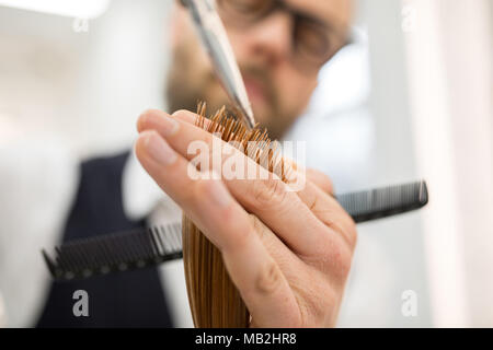 Close up portrait of hairdresser hands cutting hair ends - Stock Photo
