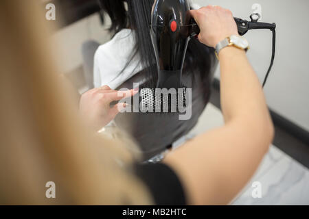 Cropped portrait of hairdresser styling customer hair with drier - Stock Photo