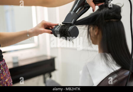 Cropped portrait of hairdresser styling customer hair with brush and drier - Stock Photo