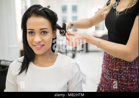 Portrait of happy woman having hair curled by hairdresser - Stock Photo