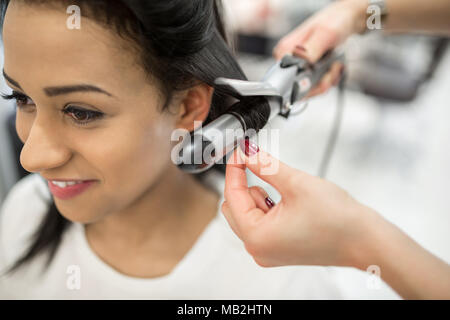 Close up portrait of happy young woman having hair stylized at hairdresser - Stock Photo