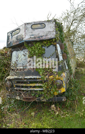 An old abandoned motor vehicle covered in overgrown ivy,moss,weeds and grass on a farm in North Somerset in the UK. Robert Timoney/Stock/Image - Stock Photo