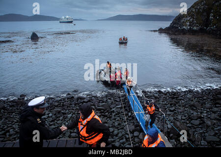 Man who works as a lighthouse keeper in the cape receives the expedition. The explorers disembark at Cape Horn, Tierra de Fuego, Patagonia, Chile - Stock Photo