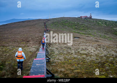 Explorers walking to lighthouse, Cape Horn, Tierra de Fuego, Patagonia, Chile - Stock Photo
