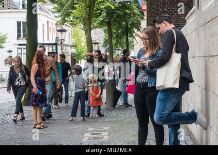 Utrecht, Netherlands - August 13, 2016: Couple of tourists checking their smartphones at a busy Dom Square. - Stock Photo