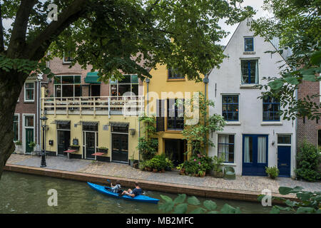 Utrecht, Netherlands - August 13, 2016: Couple canoeing along the houses on the wharf of the Oudegracht. - Stock Photo