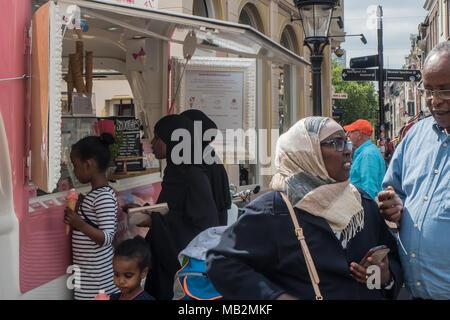 Utrecht, Netherlands - August 13, 2016: Black girls wearing headscarfs buy ice creams at the Maartensbrug. - Stock Photo