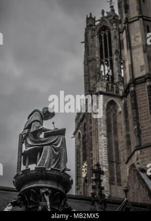 Utrecht, Netherlands - August 13, 2016: Statue of a scribe in the Pandhof. In the background the Dom Tower. - Stock Photo