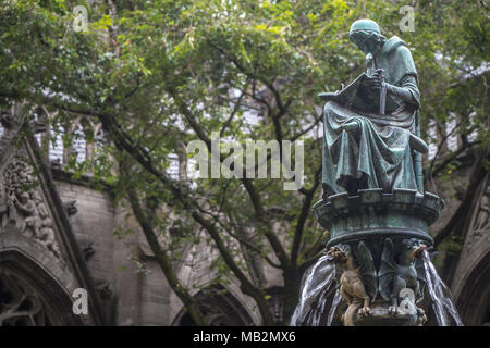 Utrecht, Netherlands - August 13, 2016: Statue of a scribe in the Pandhof. In the background a tree. - Stock Photo