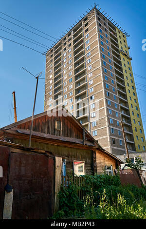 Old wooden house in front of a big tall modern skyscraper representing the concept of old vs new - Stock Photo