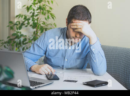 Sad man looking at his monthly bills at home. - Stock Photo