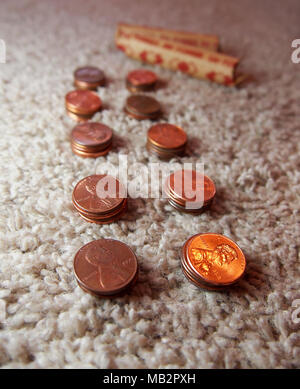 Stacks of copper American pennies are lined up on a carpet in preparation to be packed into paper rolls of 50. - Stock Photo