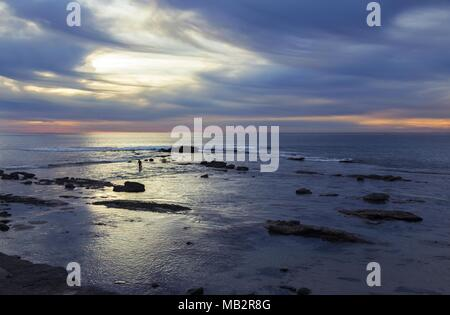 Pacific Ocean and lone Surfer Silhouette with Dramatic Sunset Sky on Windansea Beach San Diego California Coastline - Stock Photo