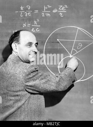 Enrico Fermi (1901–1954), Italian-American physicist and pioneer in nuclear fission, demonstates a physics equation on a chalkboard, c1950. Fermi worked on the Manhattan Project during World War II and made significant contributions to the development of quantum theory, nuclear and particle physics, and statistical mechanics. - Stock Photo