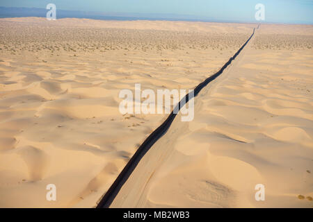 INTERNATIONAL BORDER: MEXICO - UNITED STATES (aerial view). Algodones Dunes in the Sonoran Desert, Baja California, Mexico (left of wall). - Stock Photo