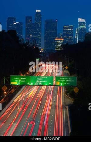 LIGHT TRAILS ON THE ARROYO SECO PARKWAY WITH DOWNTOWN LOS ANGELES IN THE DISTANCE. California, USA. - Stock Photo