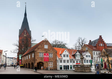 Flensburg, Germany - February 10, 2017: Nordermarkt, city square with Neptune Fountain and Sankt Marien or Saint Mary church. Ordinary people walk on  - Stock Photo