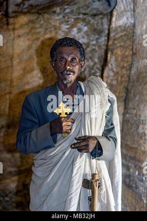 Orthodox priest inside the rock church Medhane Alem, Tigray Province, Ethiopia - Stock Photo