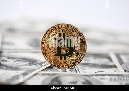 Shiny golden bitcoin as popular innovative digital money standing on old hundred dollar banknotes. Blockchain electronic web money cryptocurrency mining exchange finance trend virtual business - Stock Photo