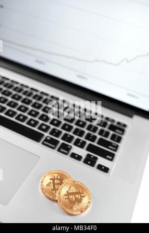 Two golden bitcoins placed on silver laptop with financial chart on its screen. Cryptocurrency virtual digital money web electronic currency blockchain future trends innovative business mining exchange - Stock Photo