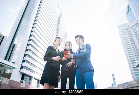 Surprised business people using smart phone outdoors . excited young businessman and business woman expressing positive while standing outdoors with o - Stock Photo