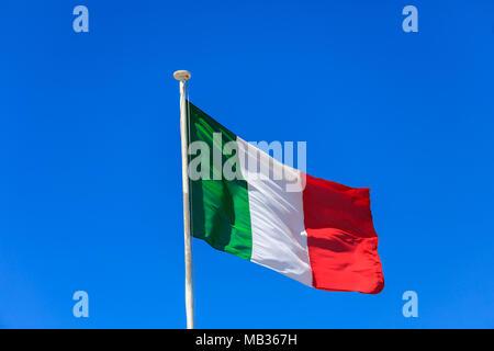 Italy flag. Italian flag on a flagpole waving on a bright blue sky background - Stock Photo