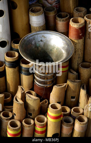Varanasi attracts many tourists, you can find many sales people along the river like someone who sells bamboo flutes - Stock Photo