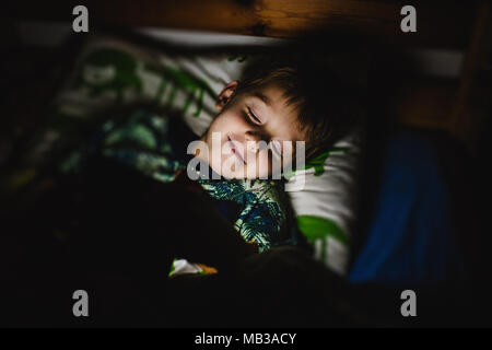 Young boy reading an electronic book with integrated light lying in bed before asleep. Daily technology in children life. Dark background, low light. - Stock Photo