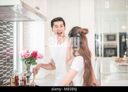 young Asian woman having her husband tasting pasta dish .happy couple in kitchen - Stock Photo
