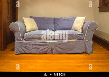 BLUE COUCH ON OAK WOODEN LIVING ROOM FLOOR - Stock Photo