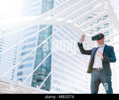 Concept Simulation Business, Smart businessman in a suit wear vr goggles with city town background. - Stock Photo