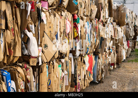 Bundles of baled cardboard are stacked and waiting for recycling. - Stock Photo