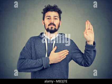 Sincere young man swearing with hand on heart - Stock Photo