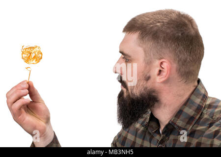 Close up portrait of attractive young serious or dangerous Caucasian man with burning match on his hand on white background. Brunette hipster in trend - Stock Photo