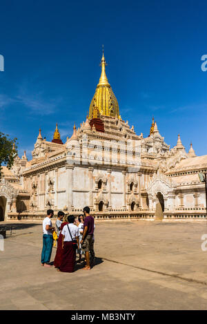 Ananda Temple vertical photo, Burmese tour guide with western tourists in foreground, in Bagan Myanmar - Stock Photo