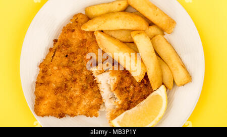 Traditional Popular Fish And Chips Against A Yellow Background With A Slice Of Lemon - Stock Photo