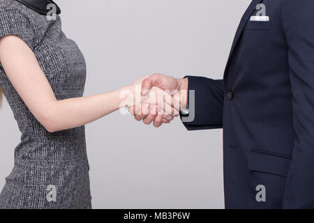 Businessman and businesswoman in formal wear handshake closeup on gray background - Stock Photo