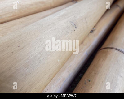 Pile of dry brown bamboo sticks with wooden texture in diagonal over green astroturf on background - Stock Photo